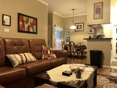 Spacious living room with a big leather sofa and recliner chair