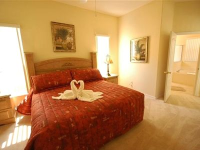 Master bedroom with king size bed and ensuite bathroom with tub and shower.