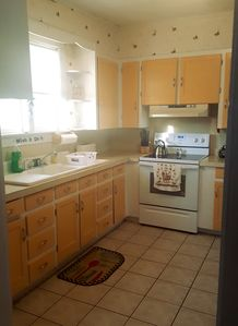 Kitchen completely outfitted with cookware, utensils, glassware and appliances.
