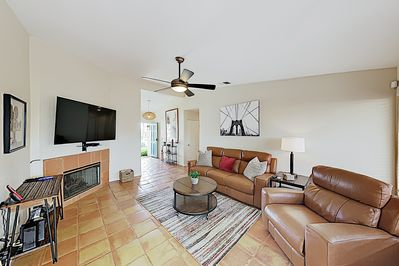 """Living Room - Sleek leather furniture, a gas fireplace, and a 65"""" smart TV set the scene for relaxation in the living room."""