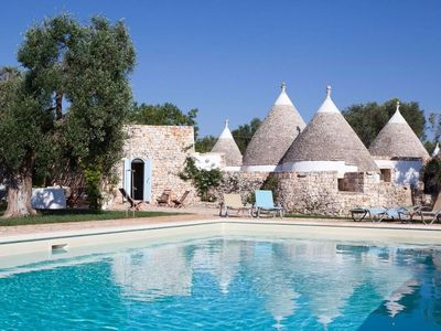 Photo for Trullo surrounded by a flower garden, the patio overlooking the pool