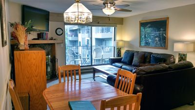 BC West J-3 Living room w/ dining table, wood fireplace, and balcony w/ gas BBQ