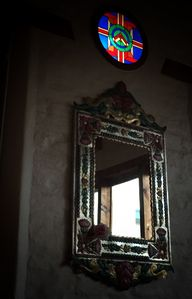 Mexican mirror and stained glass window in bedroom