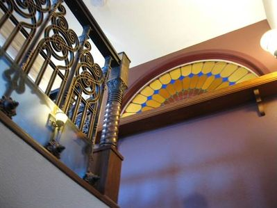 Stained Glass window and stair rail gaurd rail viewed from staircase