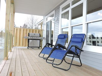 Balcony with a Gas Grill and Deck Chairs