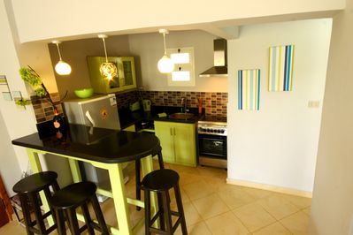 Open plan kitchen with gas oven, 4 hobs, kettle, toaster & large fridge/freezer.