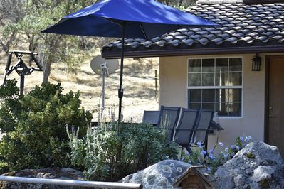 Outdoor seating for six under the shade of a new umbrella; vast hill vistas.