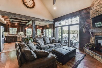 Living area with stone fireplace, huge fan, custom furniture and tall ceilings!
