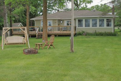 Large level yard with log swing to relax and lake side fire fit