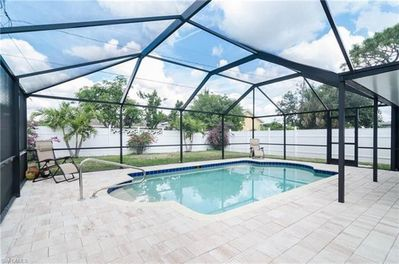 Pristine sparkling pool with screened enclosure and plenty of sunshine!