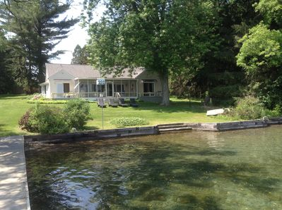 Front of house facing lake with permanent dock, steps into water