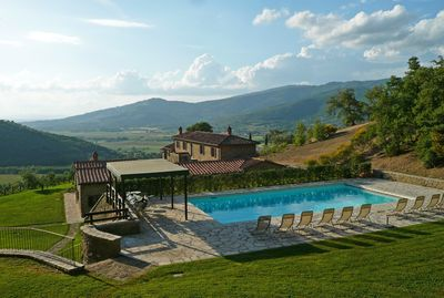 Pool, house, & garden with Tuscan farms below & medieval town of Cortona.