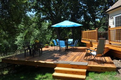 Two-level deck with table seating for ten or more, gas barbecue on upper deck.