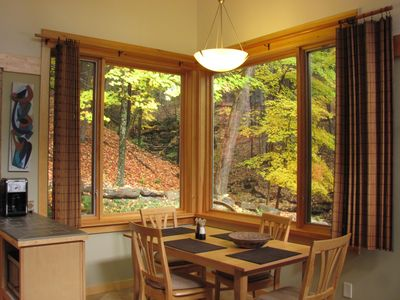 Full sized dining table off the kitchen with view of seasonal falls and stream.