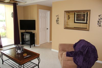 VI103 - Living with comfortable seating and flat-screen TV. Sliding doors open up to the screened in lanai with lake view.
