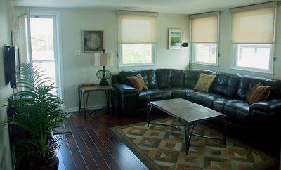 Family room with leather sectional sofa, access to deck & a flat screen TV.