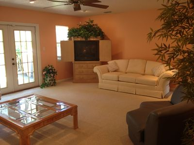 The large living room has a television with basic cable and french doors to deck