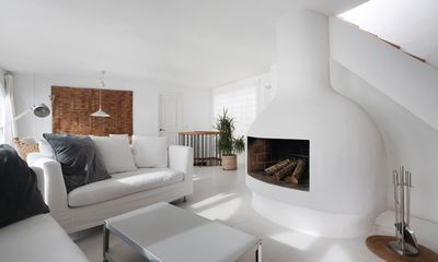 The 50m2 main living with fireplace. Stair to roof terrace
