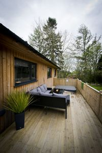 Outdoor decking area with hot tub and rattan seating.