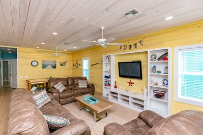 "Living Area - One of the comfiest living areas in Port A! Sink into a plush couch for a movie on the 55"" flatscreen."