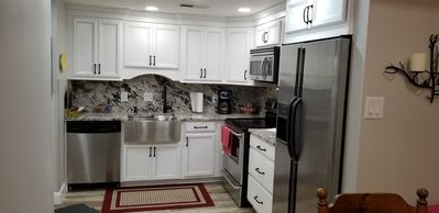 granite countertops, stainless steel appliances and farmhouse sink