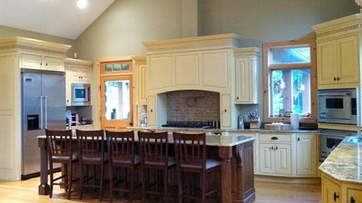 Fully-equipped gourmet kitchen adorned with granite counters & Viking appliances
