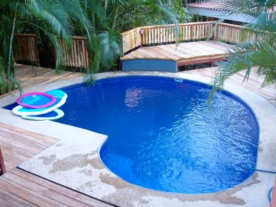Teak decking with a deep pool in a tropical jungle setting.