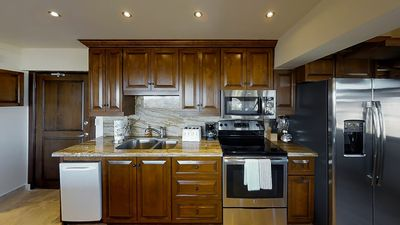 Fully equipped kitchen with electric stove, dish washer and oven.