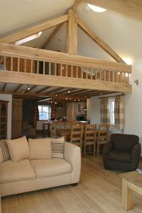 Open plan layout showing mezzanine sleeping deck above the dining area