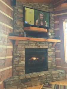 stack stone double mantel fireplace with a home theater sound system