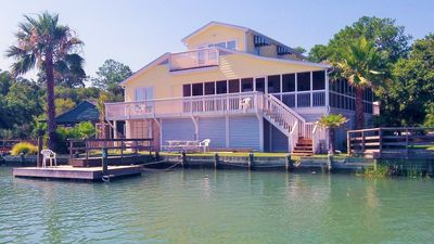 Rear of the home with decks porches and private dock