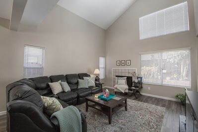 First floor living room with comfy leather sofa, high ceiling, sunny & spacious