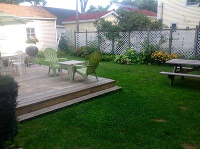 Back yard with privacy fence and picnic table is a tree shaded area.