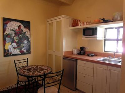 Kitchen with refrigerator, microwave 2 burner cook top and small appliances.