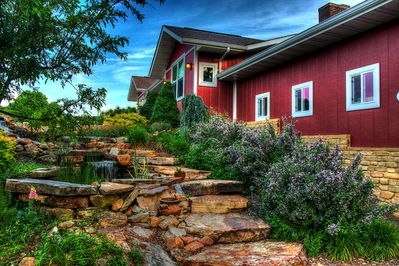 Natural stone steps lead past flowers and a waterfall to the front door.