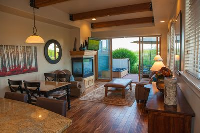 Warm, open living space with gas fireplace, wood floors, and sophisticated decor
