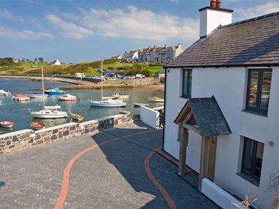 Photo for Situated right on the waterfront, and overlooking the beautiful harbour and sandy beach, this former