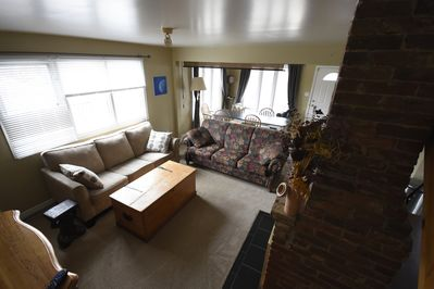 sun drenched living room and dining with gas fireplace and pull out double bed