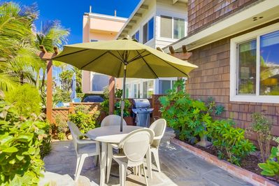 Outside patio with an ocean view, table for 4, umbrella, and a gas BBQ