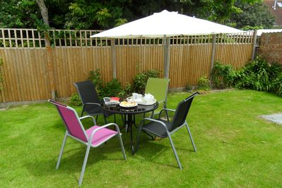 Secure rear garden with patio furniture and a large sun umbrella