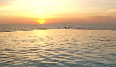 Infinity swimming pool that appears to overflow into the ocean