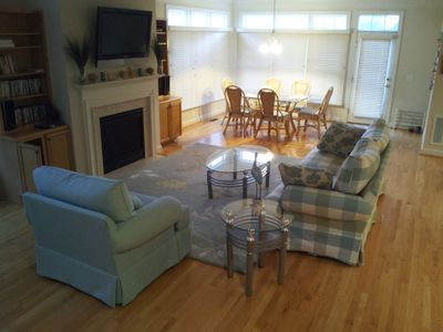Great room with hardwood floors, flat screen TV, glass tables, and gas fireplace