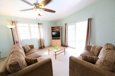 Sunny & spacious living room. French doors open to 30-foot deck w/ocean views.