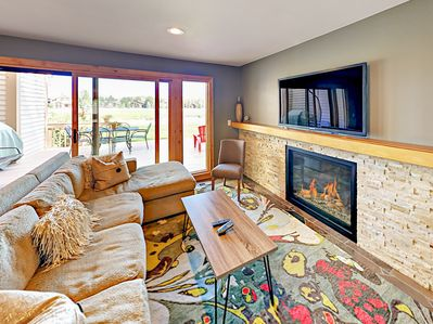 Living Area - Spanning wall-to-wall, the impressive gas fireplace with stone surround takes center stage in the living area.