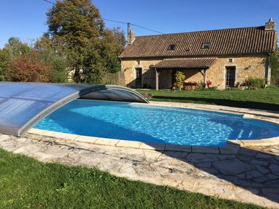 Pool in front of the house facing open fields.