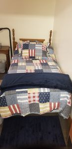 Single twin bed with pillow top mattress cover.
