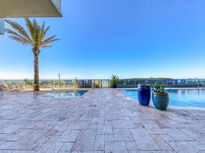 Photo for Steps to the beach from classy condo - gym, pool & hot tub available