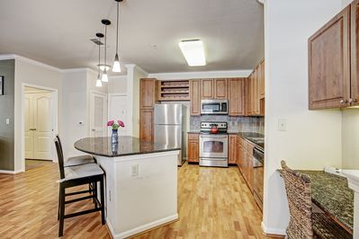 Stocked kitchen with granite countertops, electric cooktop, microwave & more