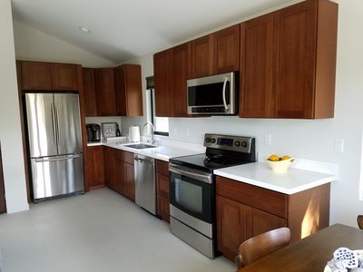 Chef's kitchen with full size stainless steel appliances and quartz countertop