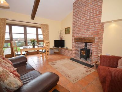 Lounge/dining area with woodburner and views towards the lake